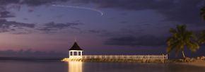 Die Langzeitbelichtung zeigt den Lichtstreif eines startenden Flugzeugs am abendlichen Himmel. Irgendwie blickt man ihm gerne nach, dem deutschen Ferienflieger. (Bildlegenden-Texte: A. Augustin)