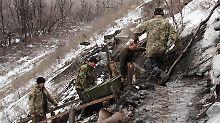 """Ukrainische Soldaten schleppen eine Munitionskiste über eine vereiste Treppe zu ihrer Stellung im """"Ameisenhügel"""" bei Donezk hinauf."""