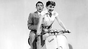 Gregory Peck und Audrey Hepburn auf einer Vespa.