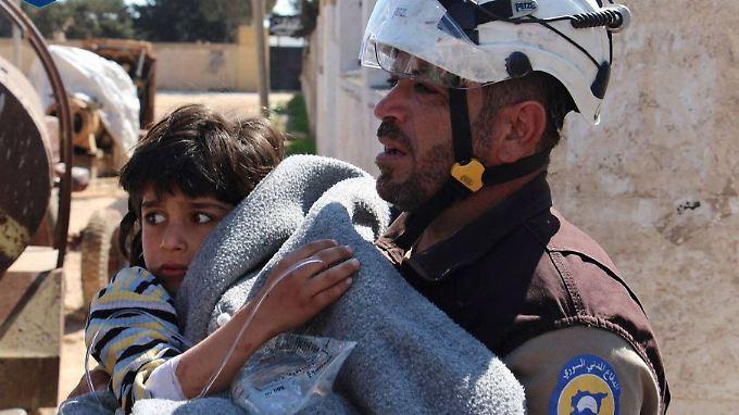 Ein Mitglied der syrischen Weißhelme rettet ein Kind aus den Trümmern.