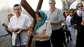 Menschen laufen am Karfreitag auf der Via Dolorosa und Gedenken dem Leiden Christi.