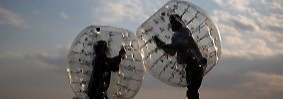 Die Spieler tragen Stelzen und befinden sich in einer Art Blase, während sie wie Sumoringer aufeinanderprallen.