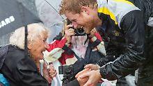 Küsschen im Regen: Prinz Harry macht sich nass