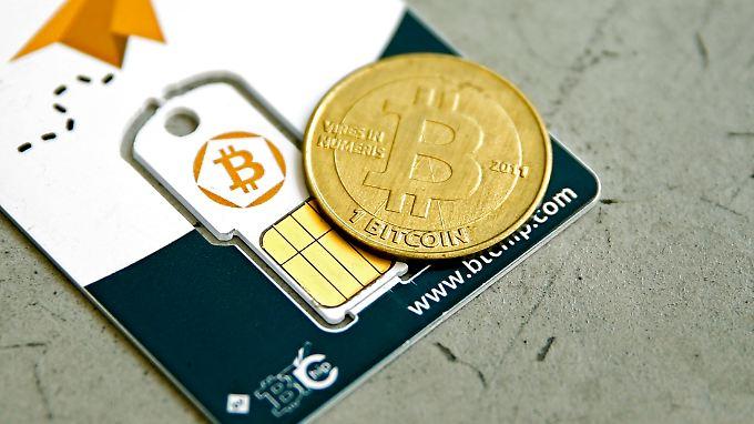 """Eine Bitcoin-Münze auf einem """"virtuellen Portemonnaie"""" in Form einer Speicherkarte."""