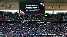 """Texthilfe für die Franzosen: """"God save the Queen"""" wird für sie auf der Stadionleinwand eingeblendet."""