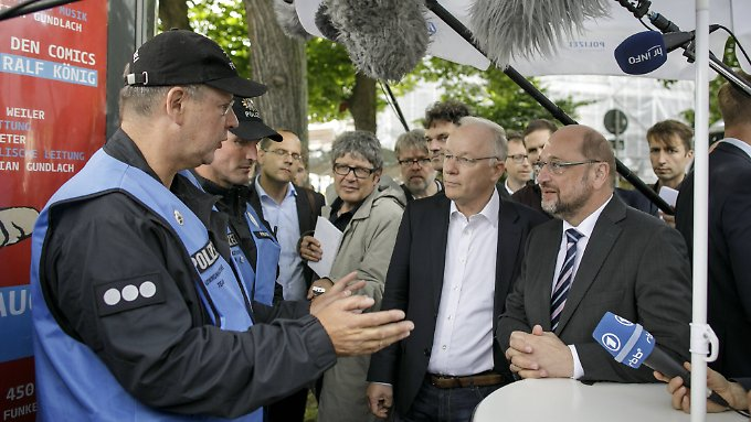 Martin Schulz im Gespräch mit Polizisten, die am Rande des Schanzenviertels an einem Infostand stehen.