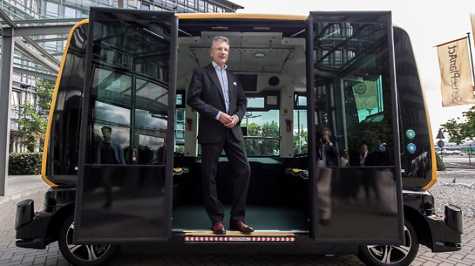 """Continental-Vorstandsvorsitzender Elmar Degenhart mit dem autonom fahrenden Taxi """"Cube""""."""