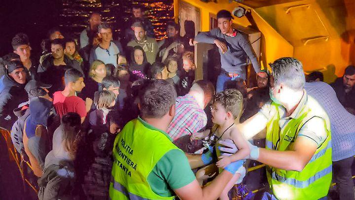 Grenzpolizisten heben im Hafen von Constanta ein Kind aus dem Flüchtlingsboot.
