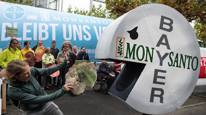Eine Demonstrantin wehrt vor der Bayer-Konzernzentrale in Leverkusen einen Pac-Man im Bayer-Monsanto-Look ab.