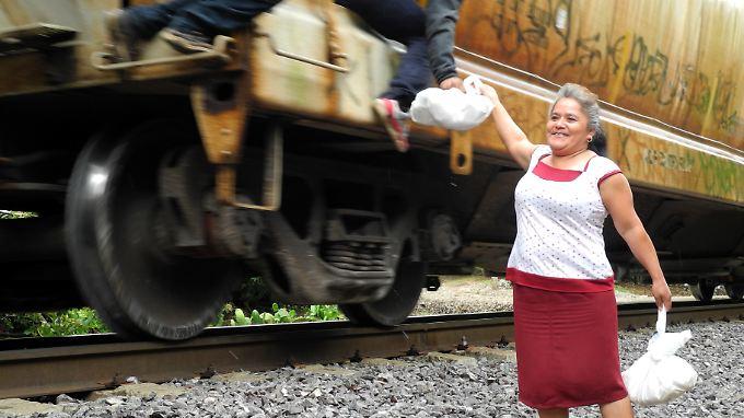 """Jetzt muss es schnell gehen, denn der Güterzug bremst nur leicht ab: Die guten Samaritas von """"Las Patronas"""" versorgen die notleidenden blinden Passagiere mit Lebensmittelpaketen und Wasserflaschen."""
