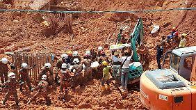 Bauarbeiter graben in Penang nach ihren verschütteten Kollegen.