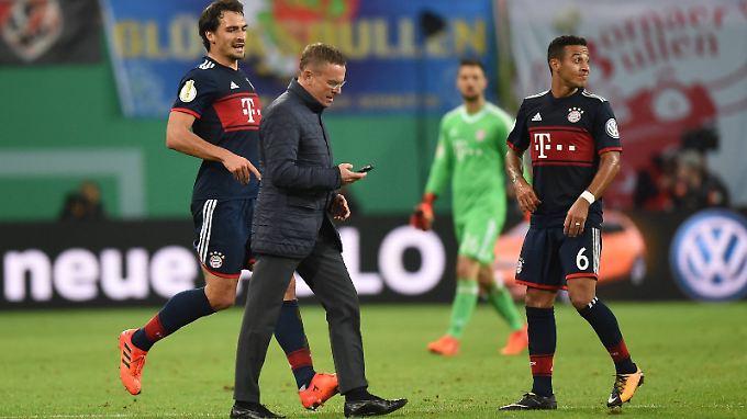 RB-Sportdirektor Ralf Rangnick eilt mit dem Handy in der Hand zum Schiedsrichter. Mats Hummels will ihn aufhalten.