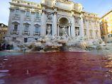 Farbanschlag eines Künstlers: Römischer Trevi-Brunnen rot gefärbt