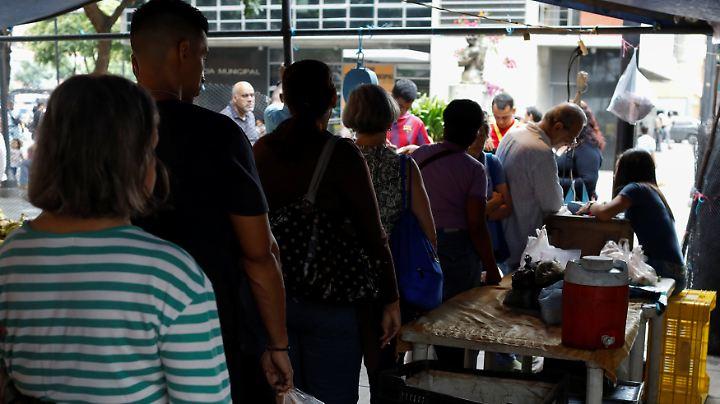 Menschen in Caracas stehen bei einer Obst- und Gemüsehändlerin an und warten auf ihre Ration.