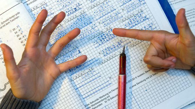 Ein achtjähriger Junge nimmt bei den Hausaufgaben im Fach Mathematik seine Finger zur Hilfe um besser zu zählen.