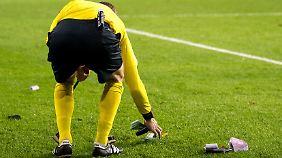 Ein Linienrichter hebt in Anderlecht das Falschgeld der Bayern-Fans auf.