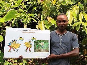 Serge, ein Mitarbeiter der Internationalen Kakaoinitiative (ICI), zeigt eine Schautafel, die er nutzt, um Dorfbewohner über die Gefahren von Kinderarbeit aufzuklären.