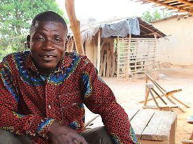 Der Kakaobauer Fabrice Amangoua, der Vater der früheren Kinderarbeiterin Moahe, sitzt im Dorf Konan Yaokro vor dem Haus der Familie. Amangoua baut drei Hektar Kakao an.