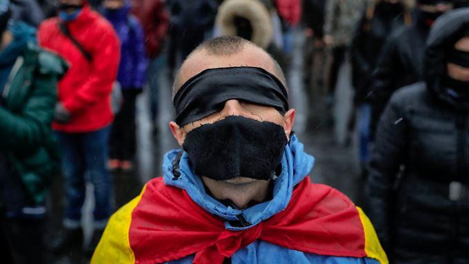 Demonstranten gegen die rumänische Justizreform verbanden sich Augen und Mund mit schwarzen Tüchern.