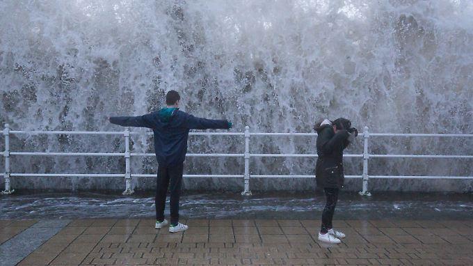 Diese Kinder stehen an einer Kaimauer in Großbritannien während vor ihnen eine Welle aufschlägt.