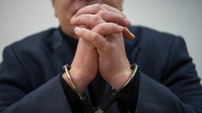 Mit Handschellen gefesselt hört der Angeklagte sein Urteil.