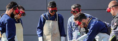 Flüchtlinge lernen in einem Ingolstädter Betrieb die Arbeit mit einem Schweißbrenner.
