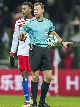 Moment mal: Schiedsrichter Felix Zwayer unterbricht die Partie im Weserstadion, nachdem Hamburger Fans einen Feuerwerkskörper auf den Rasen geworfen haben.