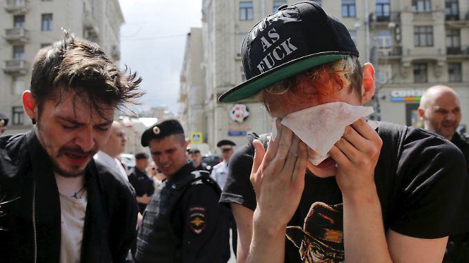"""Moskau, 30. Mai 2015: Zwei LGBT-Aktivisten kämpfen nach einer Kundgebung mit dem Pfefferspray in ihren Augen. Die Verursacher waren Gegenprotestanten aus dem """"schwulenfeindlichen Teil der Bevölkerung""""."""