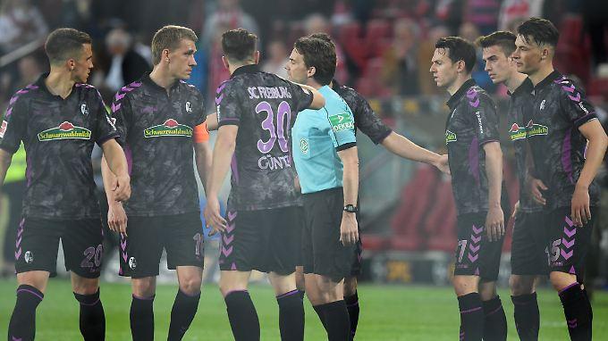 Freiburgs Spieler diskutieren mit Schiedsrichter Guido Winkmann.
