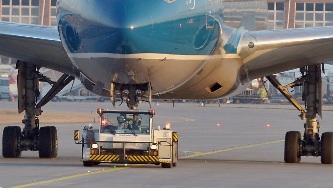 Schleppfahrzeuge ziehen am Flughafen Passagiermaschinen in ihre Parkpositionen (Archivbild).