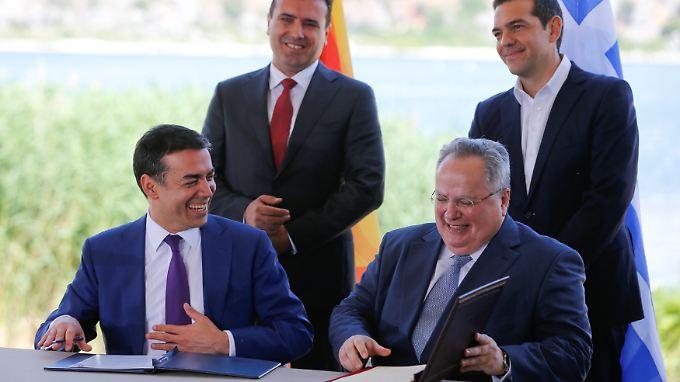 Historischer Moment: Mazedoniens Außenminister Nikola Dimitrov (l.) und sein griechischer Amtskollege Nikos Kotzias unterzeichnen vor den Augen ihrer Regierungschefs das Namensabkommen.