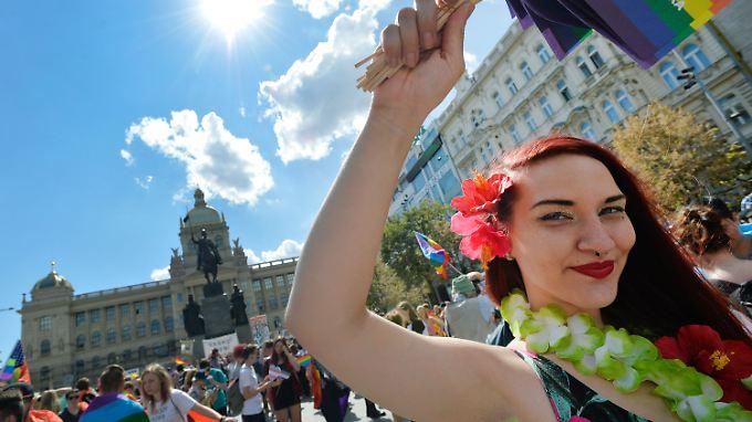 Eine Pride-Teilnehmerin schwingt die Regenbogenfahne auf Prags Straßen.