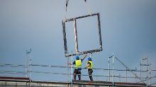 Zwei Bauarbeiter arbeiten auf einer Baustelle in der Hafencity in Hamburg.