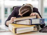 Power Nap gefällig? Eine Frau hält ein Mittagsschläfchen auf ihren Unterlagen.