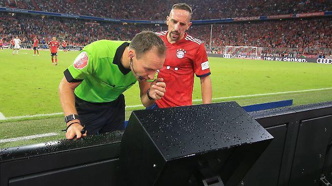 Auch Ribéry ist neugierig auf die Bilder der Strafraumszene, wird allerdings vom Schiedsrichter umgehend weggeschickt.