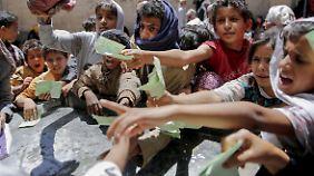 Kinder zeigen Dokumente vor, um eine Essensration durch eine lokale Wohltätigkeitsorganisation zu erhalten.