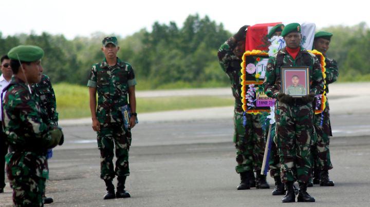 Selbst bei den Bergungsarbeiten soll es zu Angriffen durch Rebellen  gekommen sein: Indonesische Soldaten tragen den Sarg einer ihrer Landsmänner.