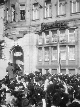 """19. März 1970: Bundeskanzler Willy Brand zeigt sich am Fenster des Hotels """"Erfurter Hof"""", direkt gegenüber des Hauptbahnhofs, den ihm zujubelnden DDR-Bürgern."""
