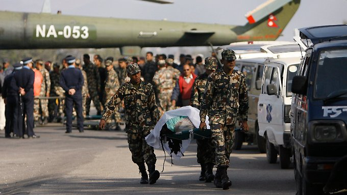 Soldaten transportieren den Leichnahm eines Opfers.
