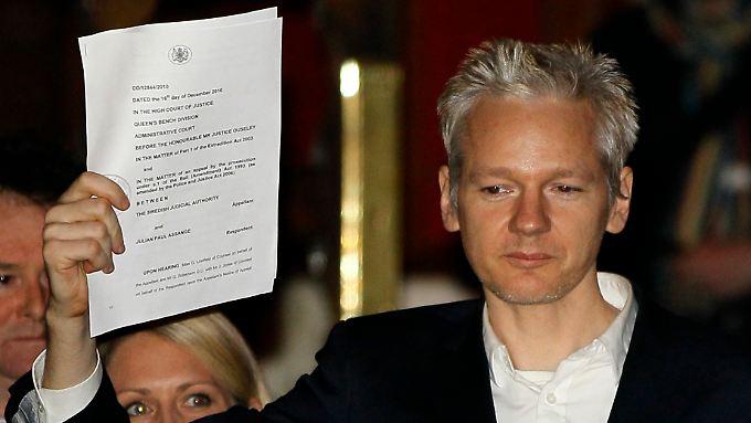 Julian Assange kurz nach seiner Freilassung. Er zeigt der versammelten Presse eine Gerichtsurkunde.
