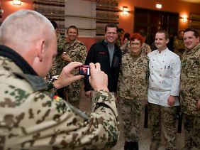 Bundeswehrsoldaten lassen sich in Masar-e-Sharif zusammen mit dem Minister ablichten.