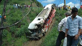 Rettungskräfte bergen den völlig zerstörten Bus.