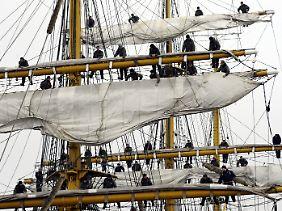 """Matrosen des Marine-Schulschiffs """"Gorch Fock"""" entern in die Takelage auf, um die Segel auszupacken (Foto: 2009)."""
