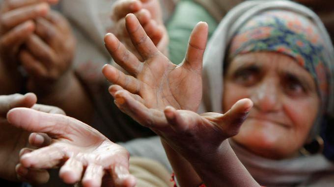 Im indischen Jammu bitten Hungernde um Essen.