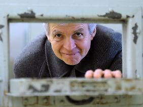 Der ehemalige Stasi-Häftling Gilbert Furian blickt durch die Türklappe einer Zelle in der Stasi-Gedenkstätte Berlin-Hohenschönhausen.