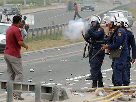In Bahrain feuert ein Polizist ein Gummigeschoss ab.