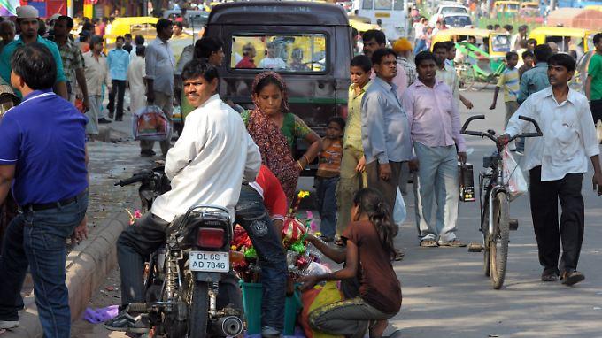 Verhältnis von 113 zu 100: Männer und Frauen auf einer Straße in Deu Delhi, Indien.