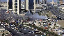 Rauch steigt auf, als Sicherheitskräfte den Perlenplatz in Manama evakuieren.