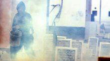 Ein Demonstrant versucht, einen Brand mit Sand zu löschen.