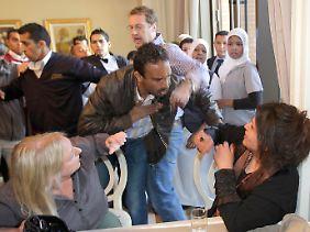 Ein Mitarbeiter des libyschen Informationsministerium bedrängt Iman al-Obeidi. Der Reporter Charles Clover versucht, ihn zurückzuhalten.